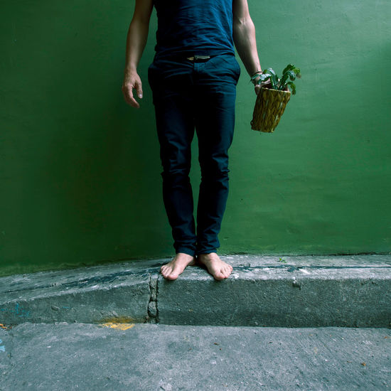 Low section of man with potted plant standing on footpath