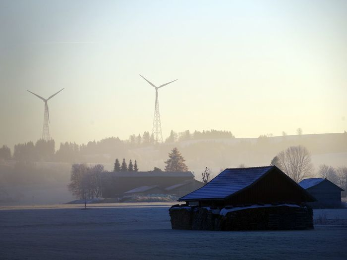 Wind turbines on snow covered landscape against sky