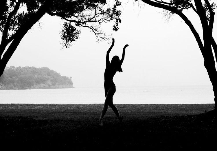 Silhouette woman dancing on field against sea