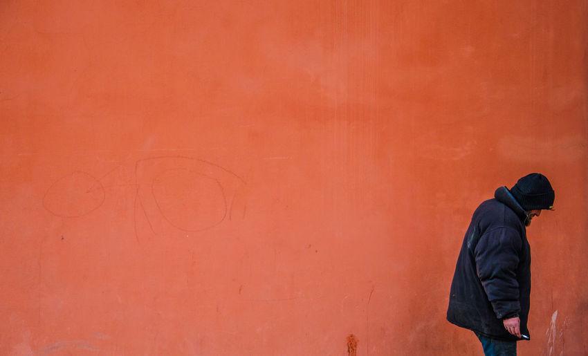 Man Standing Against Orange Wall