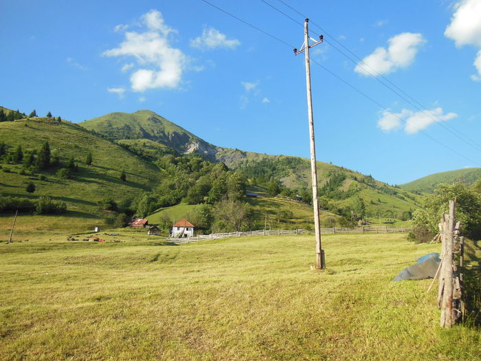 Electric pole on green landscape by mountain against sky