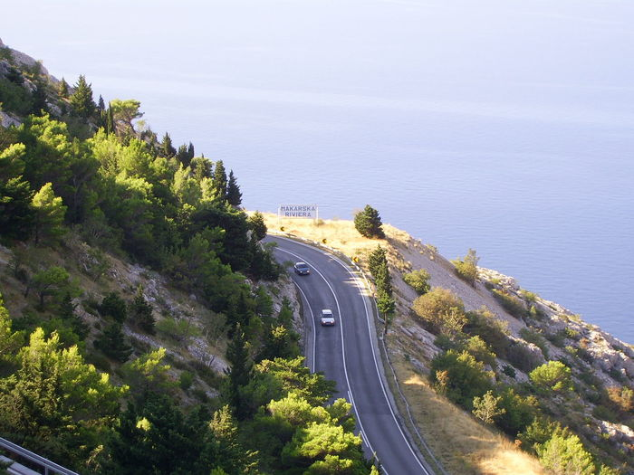 beach bay in croatia in summertime Croatia Road Summertime Beach Beauty In Nature Car City Day High Angle View Highway Mode Of Transportation Motion Nature No People on the move Outdoors Plant Road Scenics - Nature Sea Serpentine Summer Transportation Tree Water Waterfront