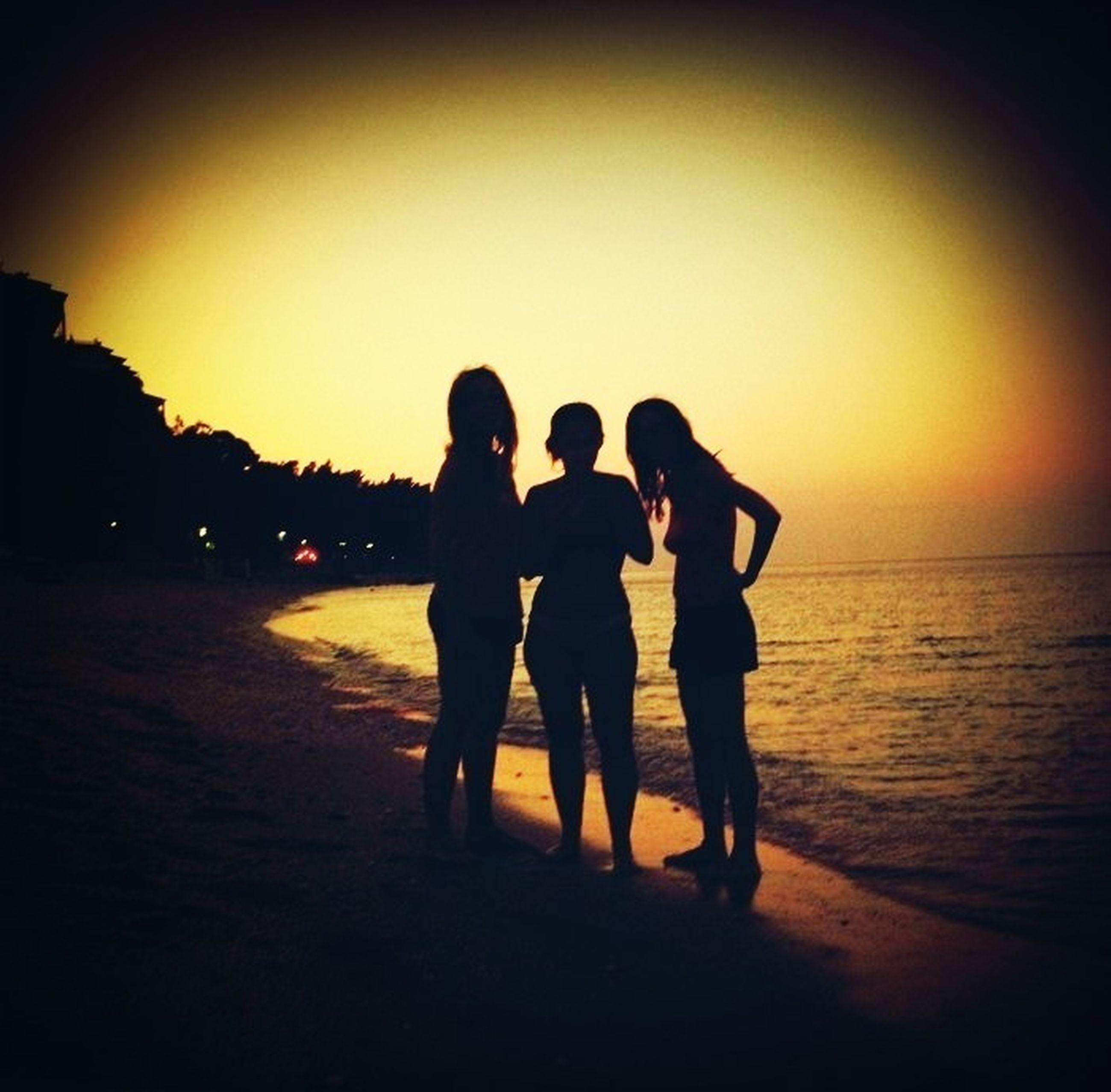 sunset, silhouette, togetherness, orange color, men, lifestyles, leisure activity, bonding, sea, beach, friendship, water, sun, sky, love, copy space, person, standing