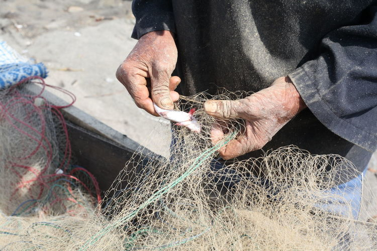 Midsection of man removing fish from net