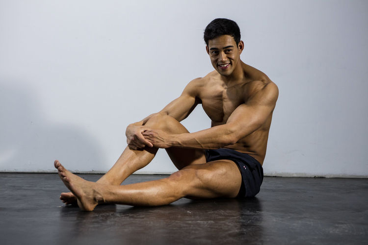 Muscular male fitness model sitting on the floor taking a break. Full body shot. Adult Asian  Athlete Body & Fitness Human Body Looking At Camera Man Nam Vo Shirtless Sitting Sportsman Taking A Break Fitness Model Full Body Shot Grey Wall Handsome Hunk Male Muscle Muscular Build One Person Smiling Strong Studio Shot Torso