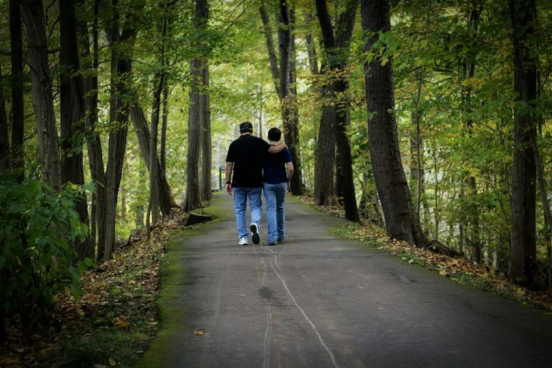 Rear view of grandfather and son walking on road amidst trees at forest