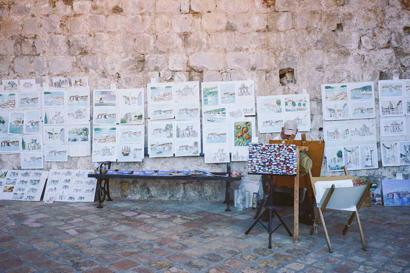 Artist on the street Seat Wall - Building Feature Chair Architecture Wall No People Built Structure Creativity Table Absence Brick Wall Day Map Brick Outdoors Flooring Furniture Relaxation Multi Colored Easel Game Of Thrones Old Town, Dubrovnik.