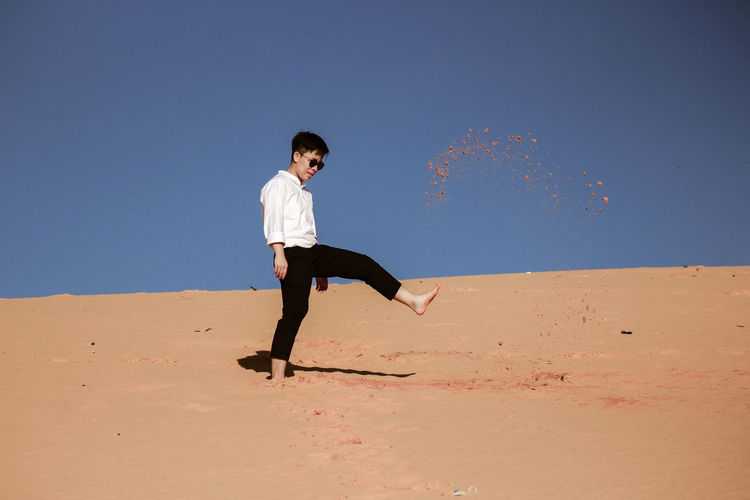 LGBT Kicks the sand, annoyance, aggression Desert Vietnam Sand Full Length Land One Person Sky Nature Casual Clothing Males  Child Men Clear Sky Leisure Activity Day Beach Childhood Desert Blue Lifestyles Side View Arid Climate Climate person Summer Nature Kick Adult Outdoors Travel Desert Action Human Representation Relaxation Happiness Enjoyment Motion Vacations Happy Beautiful Standing Sport Fun Relaxing Holiday Playing Footpath Foot Dune Portrait Adventure Emotion