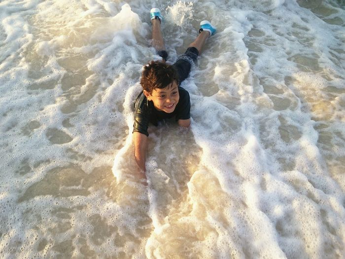 Full length of smiling boy swimming in sea during sunny day