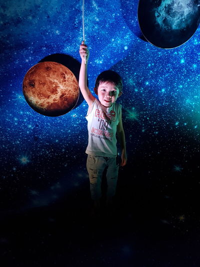 Full length of boy standing against galaxy
