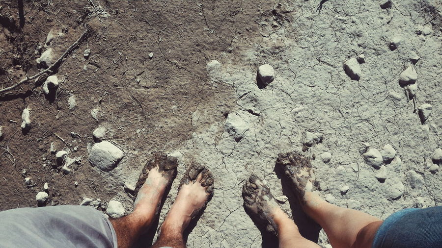 Directly above shot of muddy feet on beach
