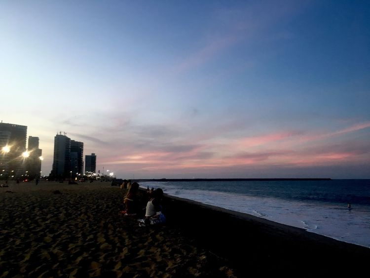 Beach Sea Sand Shore Architecture Sky Sunset Water Built Structure Building Exterior Horizon Over Water Nature Skyscraper City Vacations Outdoors Scenics Real People Beauty In Nature Day
