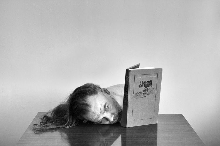 Portrait of woman sleeping on wall at home