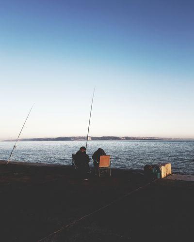 Men fishing in sea against clear sky