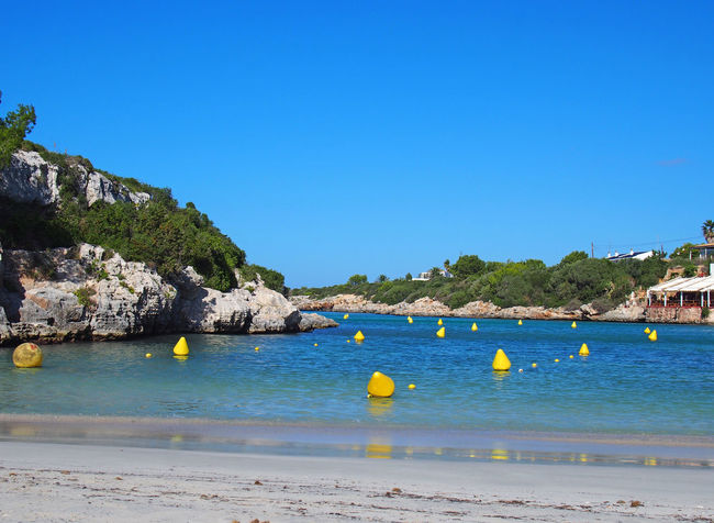 scenic view of the beach and bay at Cala Santandria in Menorca with yellow boat markers in a bright blue sunlit sea and surrounding rocks Ciutadella Vacations Relaxation Idyllic Beach Sky Water Clear Sky Scenics - Nature No People Blue Sea Land Resort Travel Summer Copy Space Outdoors