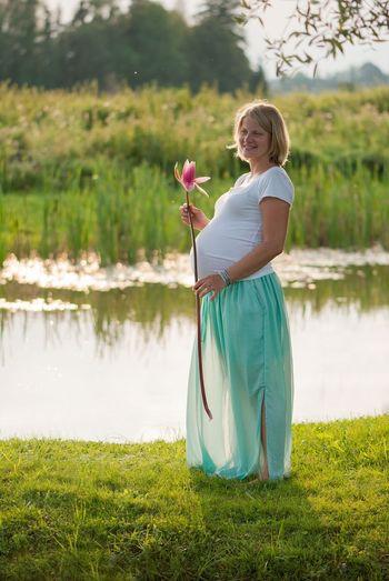 Pregnant woman standing by lake