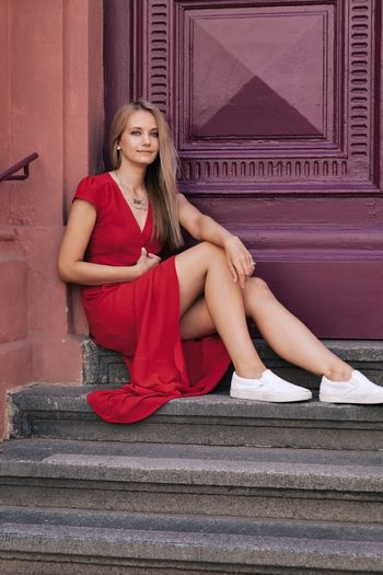 Portrait of woman sitting on steps against closed doors