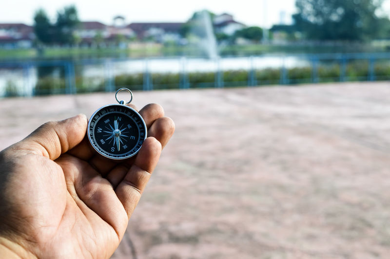 Hand holding compass with outdoor blurred background. Arrow Blurred Expedition Geography Green Travel Azimuth Background Compass Device Screen Direction Equipment Finger Foward Guide Hand Holding Metal Outdoors Outside People Summer Tourism Way Wenderful