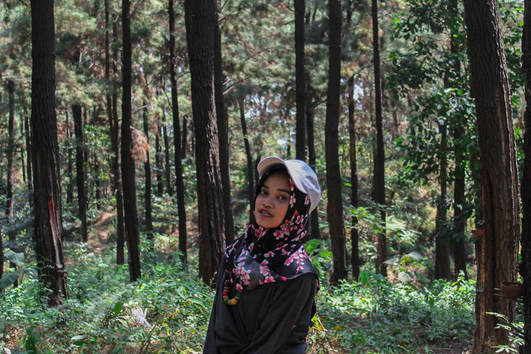 Portrait of woman standing against trees in forest