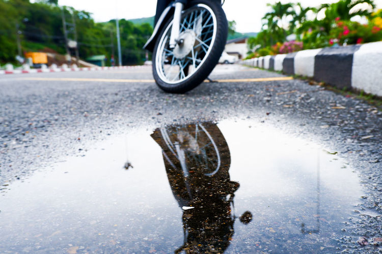 Motorcycle reflecting in puddle on road