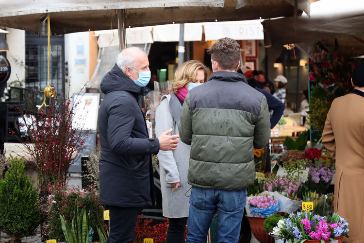 People standing in front of potted plants