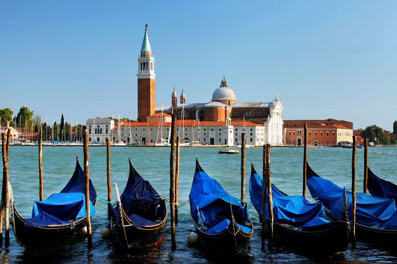 Gondolas moored in grand canal with church of san giorgio maggiore in background