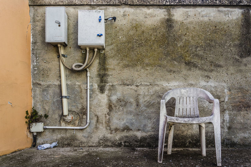Abandoned old plastic empty chair, conceptual photo Old Wall - Building Feature Architecture No People Seat Electricity  Chair Wall Indoors  Abandoned Dirt Entrance Built Structure Dirty Day Metal Door Obsolete Cable Power Supply