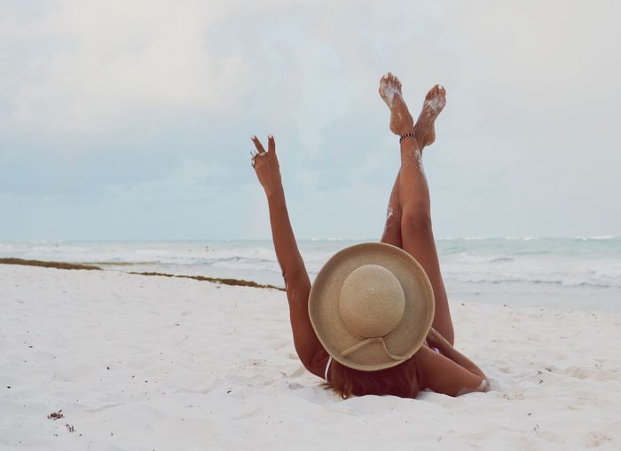 Rear View Of Bikini Woman Showing Peace Sign While Relaxing At Sandy Beach