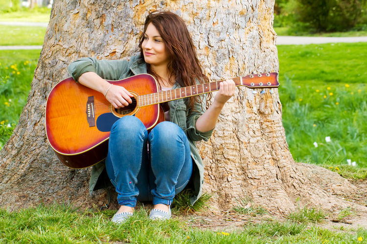 Fun Happy Woman Country Music Girl Grass Guitar Guitarist Instrument Leisure Leisure Activity Music Music School Musical Instrument Musician Nature Outdoors Park Playing Portrait Sitting Smiling Teenager Tree Tree Trunk