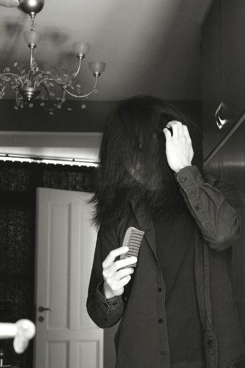 Young woman wearing jacket combing hair at home