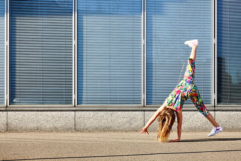 Upside down image of girl by wall outdoors