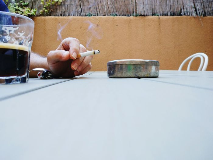 Cropped Hand Of Man Holding Cigarette By Tea At Table