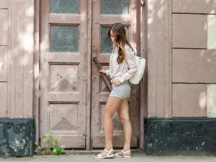 Full length of woman standing against door