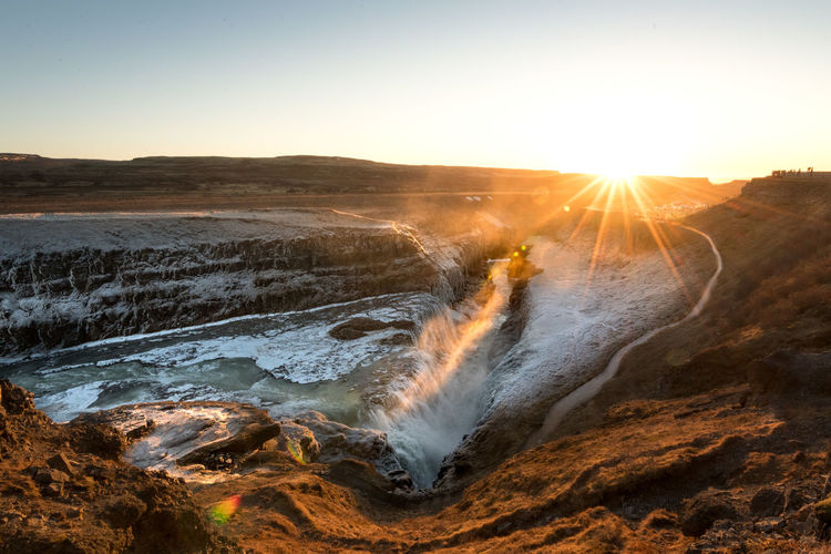 Sky Sunset Sun Beauty In Nature Nature Scenics - Nature Lens Flare Water Sunbeam Sunlight No People Rock Tranquility Land Sea Motion Tranquil Scene Environment Rock - Object Outdoors Gullfoss Waterfall Iceland
