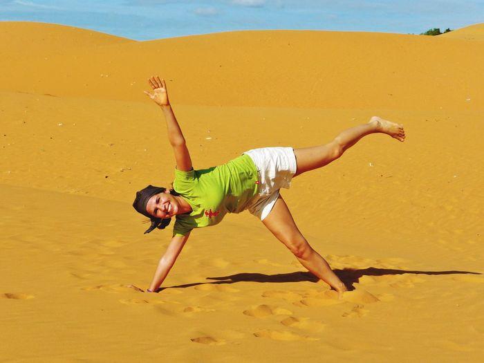 Full length portrait of happy woman enjoying in desert at mui ne bay