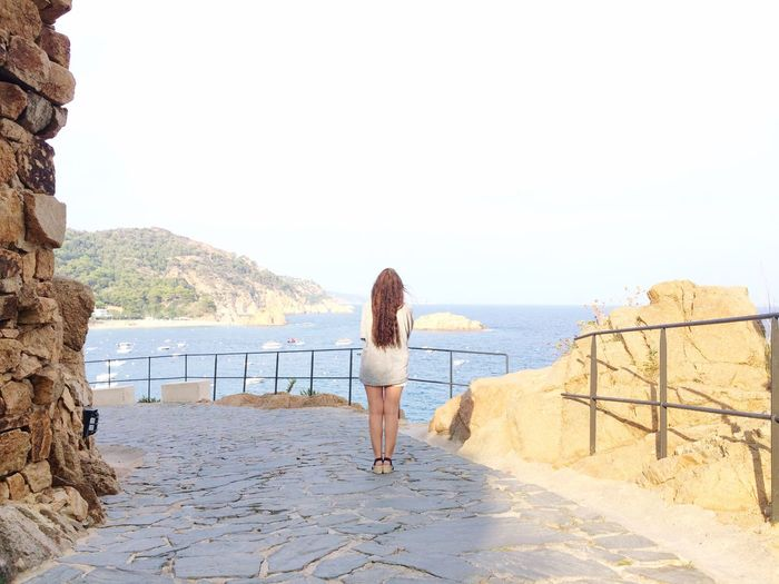 Rear view of woman looking at sea while standing on observation point at tossa de mar