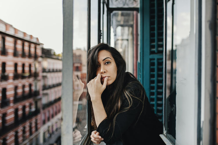 Portrait of beautiful young woman standing against window