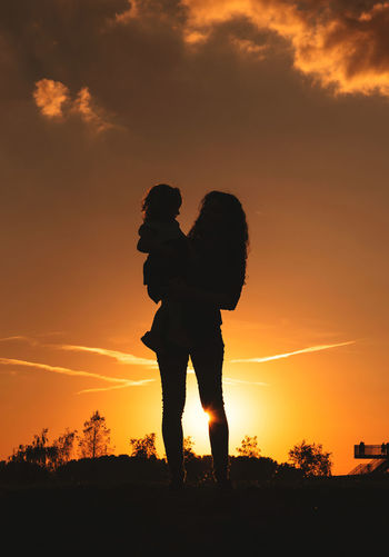 Silhouette woman carrying baby while standing on land against orange sky