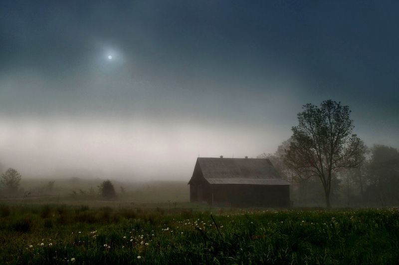 House on field against sky during foggy weather