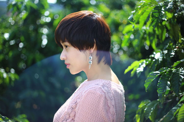 Side view of young woman by plants