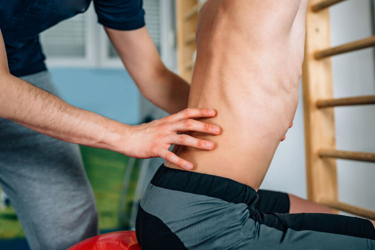 Midsection of therapist massaging men