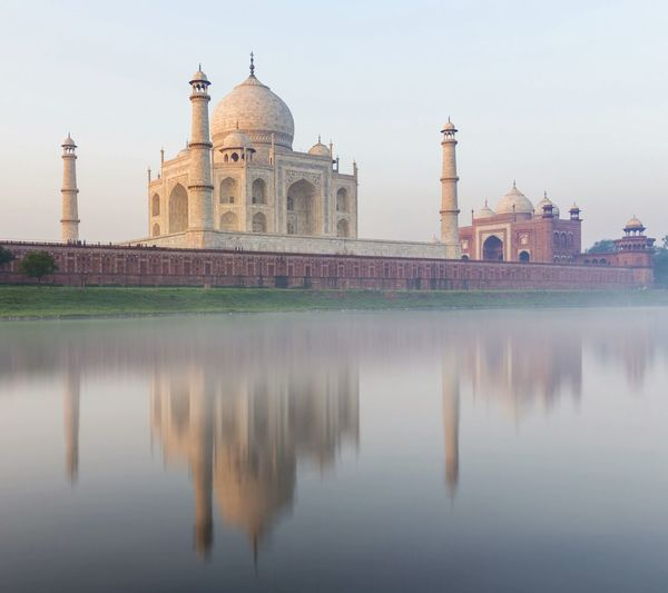Taj mahal reflecting on yamuna river in city