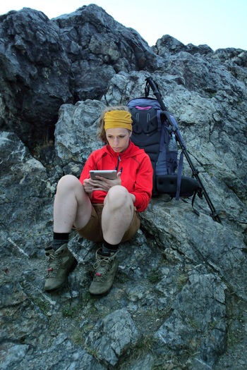 caucasian female hiker using portable tablet technology outdoors on a alpine hiking trail Alpine Backpacking Camping Expedition Freedom Hiking Tablet Travel Trekking Woman Youth Adventure Battery Connection Day Female Front View Hobby Internet Leisure Activity Lifestyles Looking At Camera Men Mountain Nature Navigation One Person Outdoors People Portable Information Device Portrait Real People Rock Rock - Object Rock Climbing Rock Formation Sitting Solid Sport Technology Trail Wireless Technology