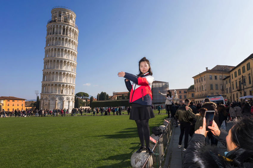 Pisa, Italy - February 11, 2018: Asian girl poses for a picture with the famous Tower of Pisa in the background, in Piazza dei Miracoli crowded with tourists. Campo Dei Miracoli Take Photos Torre Di Pisa (Italia) Tourist Asian Girl Casual Cloting Famous Place Girl Photography Portrait Posing For The Camera Selfie Smiling Tower Tower Of Pisa Travel Destination