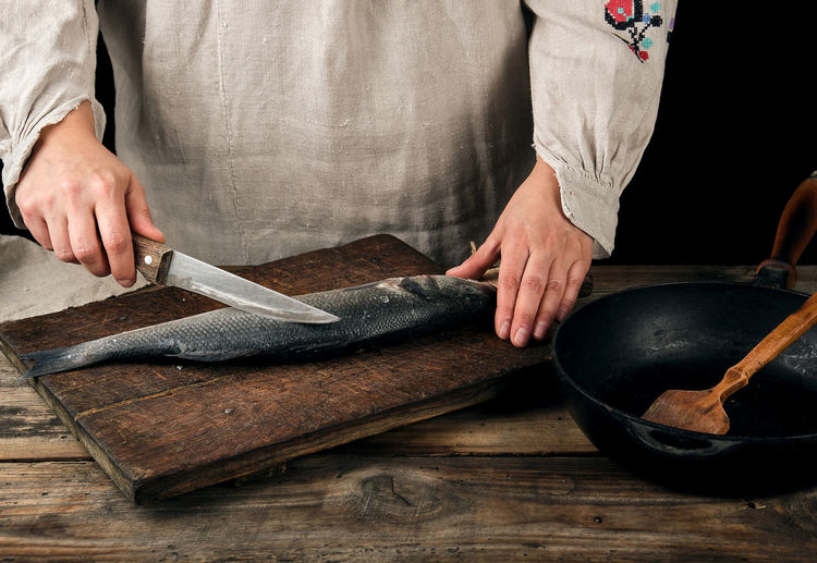 Midsection of woman cutting fish on board in kitchen