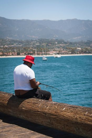 Fisherman's Wharf Wharf Fishing One Person Sitting Red Hat Hat Water Day Real People Cap Sea Nautical Vessel Outdoors Full Length Beauty In Nature Mountain Adult People Fishing Rod Bait Fishing The Week On EyeEm EyeEmNewHere