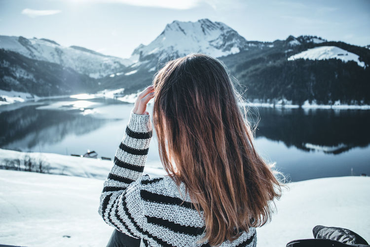 Woman against snow covered mountains and sky during winter