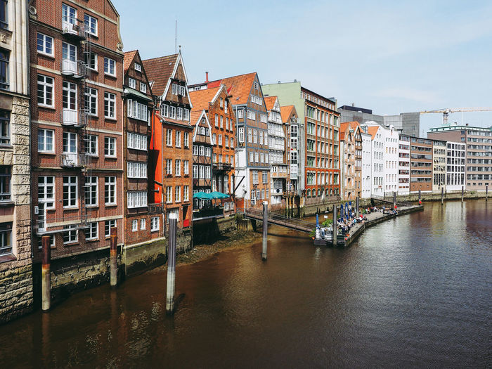 Buildings By Canal Against Sky In City