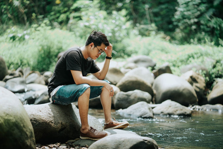 Side view of man sitting on rock by river