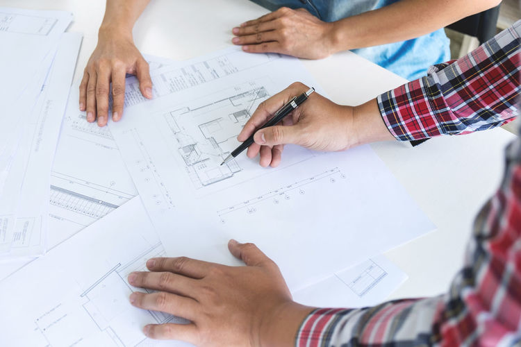 Cropped hands of male architects with blueprints at desk